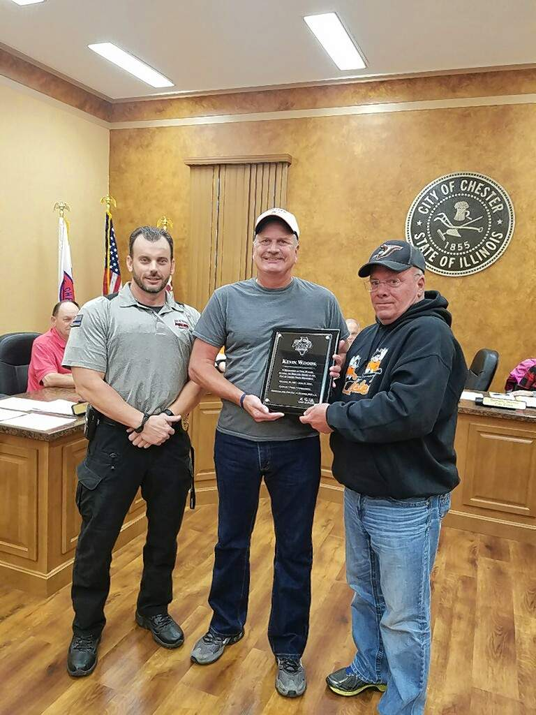 Chester Police Chief Ryan Coffey, left, and Mayor Tom Page, right, present retiring part-time Officer Kevin Woods with a plaque honoring Woods for his 30 years of service with the city.