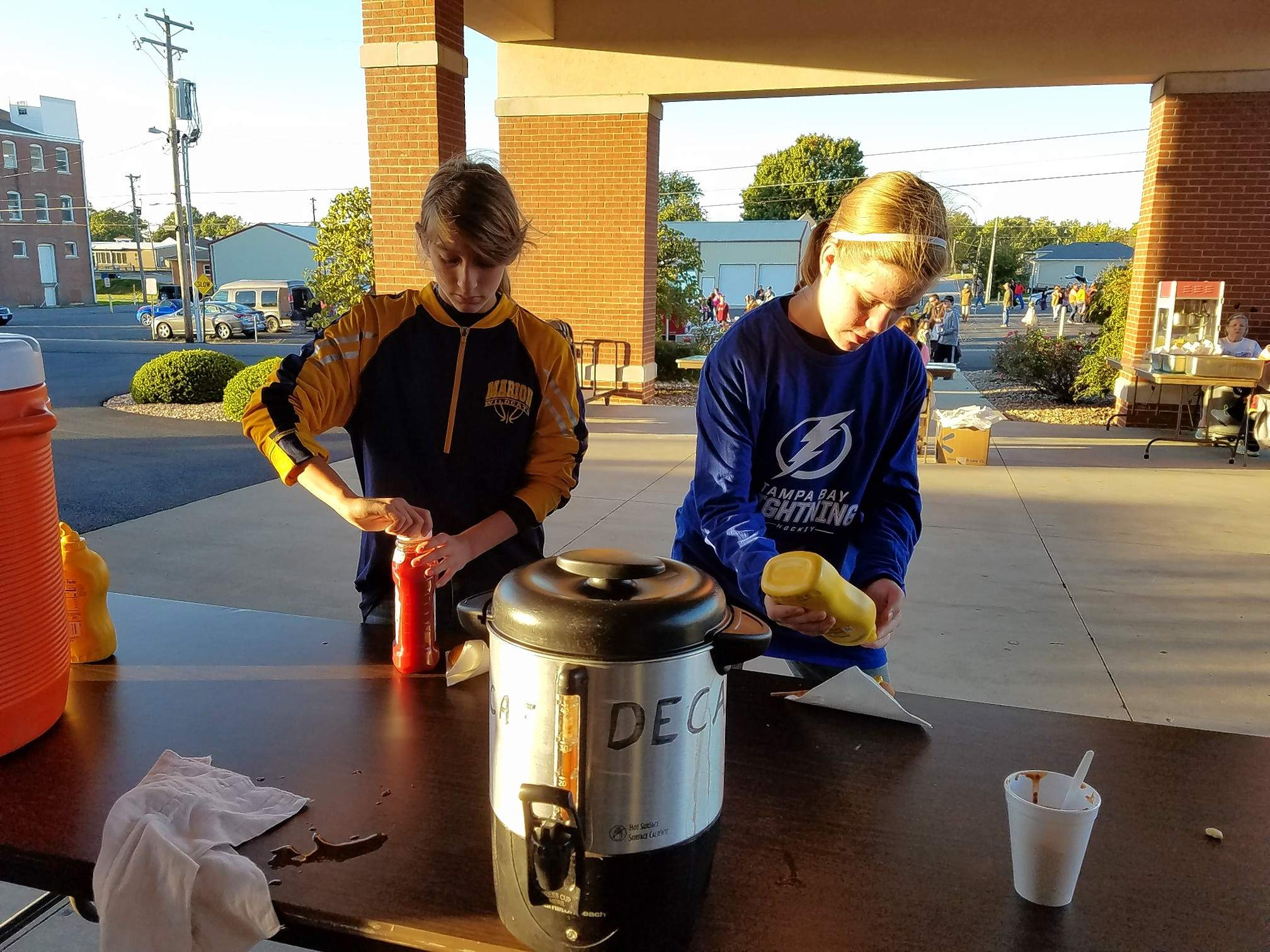 Kamryn Shill, 13, and Alexis Ucci, 13, both seventh-graders at Marion Junior High School, get condiments for their corn dogs and chili at the annual Halloween celebration at the First Baptist Church of Marion Saturday.