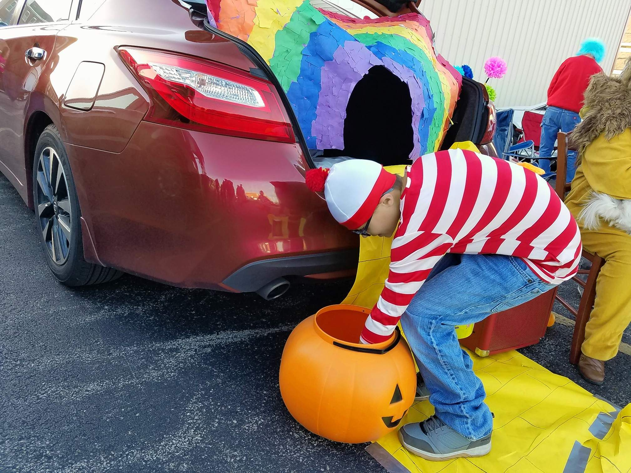 Sebastian Goff, 11, dressed as Waldo from Where's Waldo, gets his hands on some candy Saturday at the Halloween celebration hosted by the First Baptist Church in Marion.