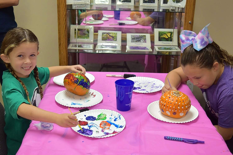 Kinzley Stewart and Adalyn Stewart paint their pumpkins at Harrisburg District Library Saturday.