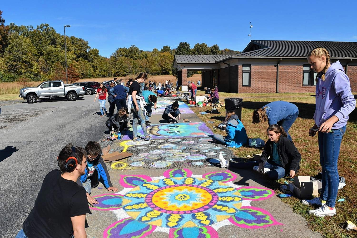 Students view their chalk art at the Harrisburg High School chalk contest Monday.