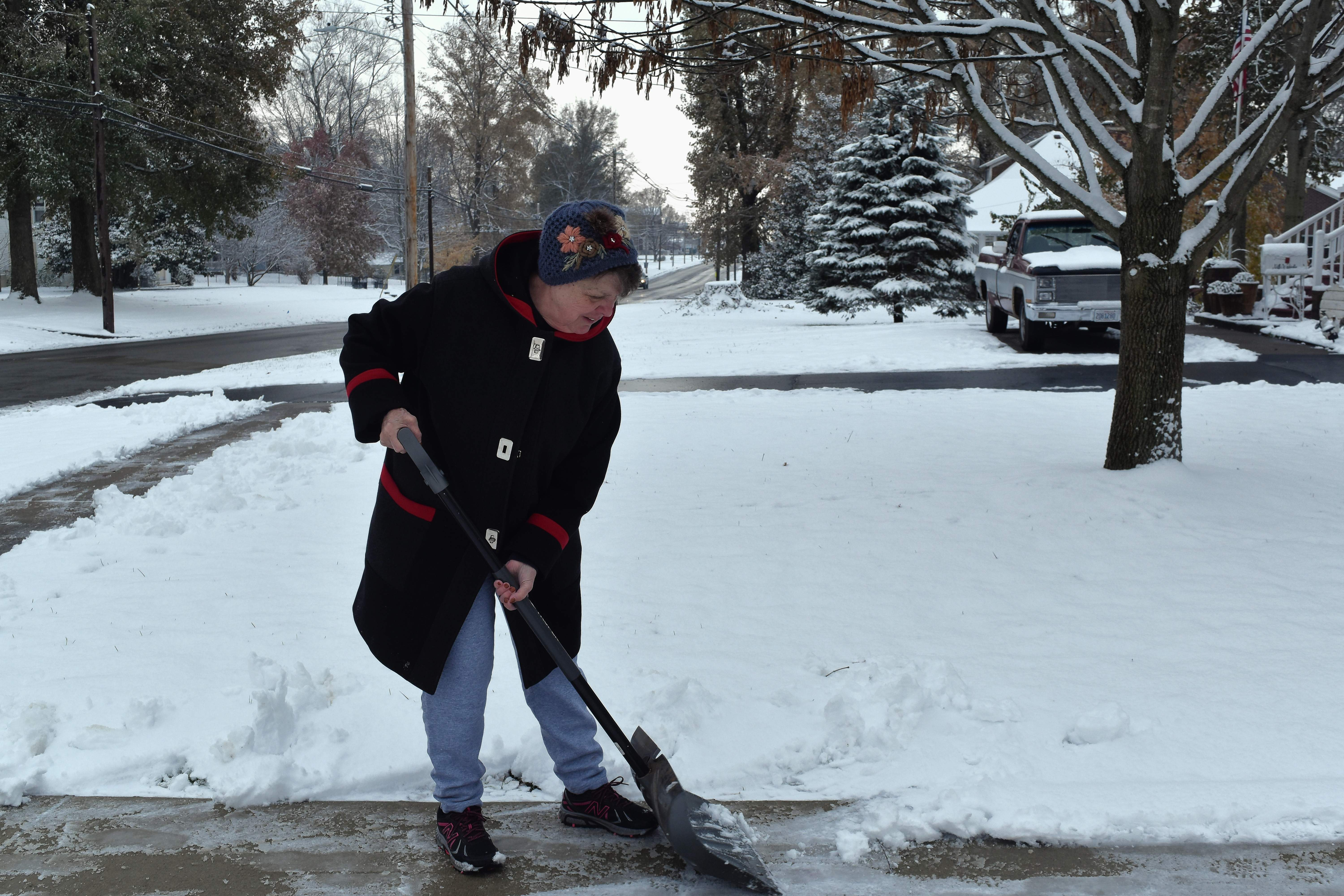 Nancy Grosse of 325 N. Washington St. in Du Quoin works hard Thursday morning to clear the sidewalk in front of her house.