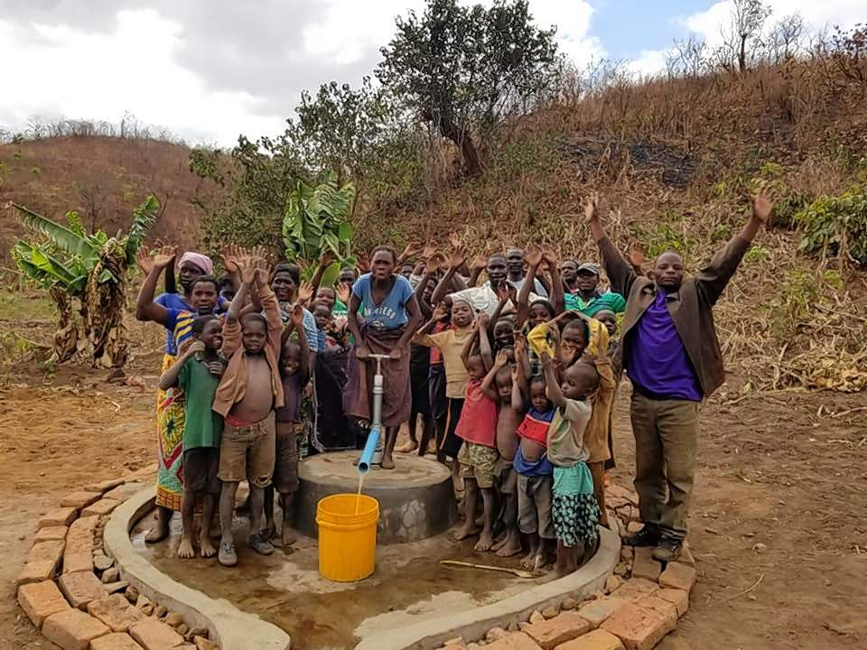 A team of villagers pumps fresh drinking water from a newly finished well near a village in the mountains of northern Malawi.