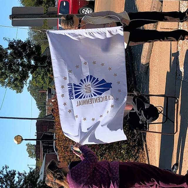 Pictured raising the flag are club member and library board member Susan Justice (left) and Library Assistant Director Mariam Richardson.