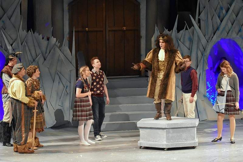 """Aslan, portrayed by Braden Cummins (on pedestal), returns near the end of the musical """"Narnia"""" staged at SIC."""
