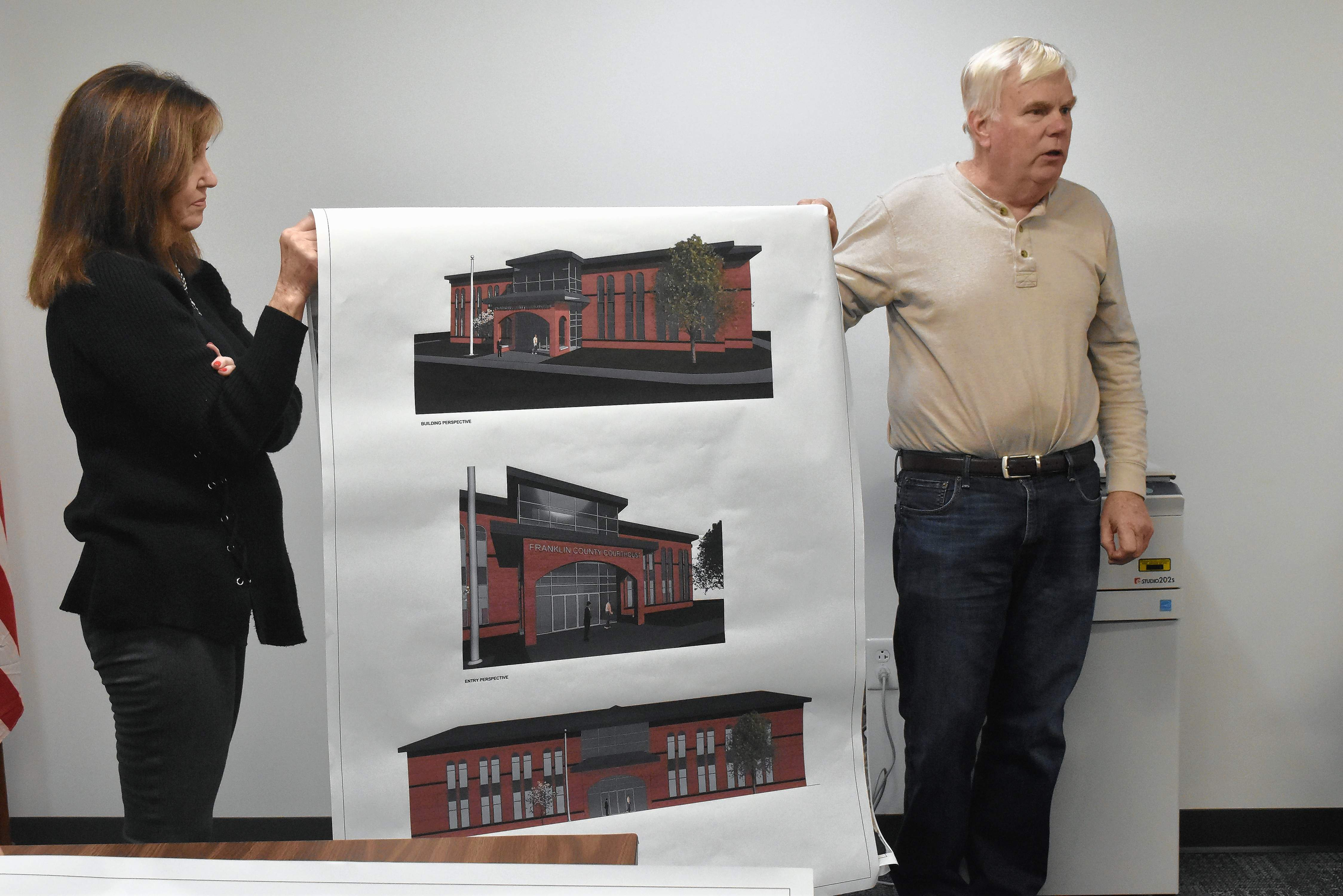 Franklin County Chairman Randall Crocker, right, and administrative assistant Gayla (Sink) Prather show an artist's rendering of what a new Franklin County Courthouse could look like. County officials are proposal to tear down the current one and build a new structure on the same property.