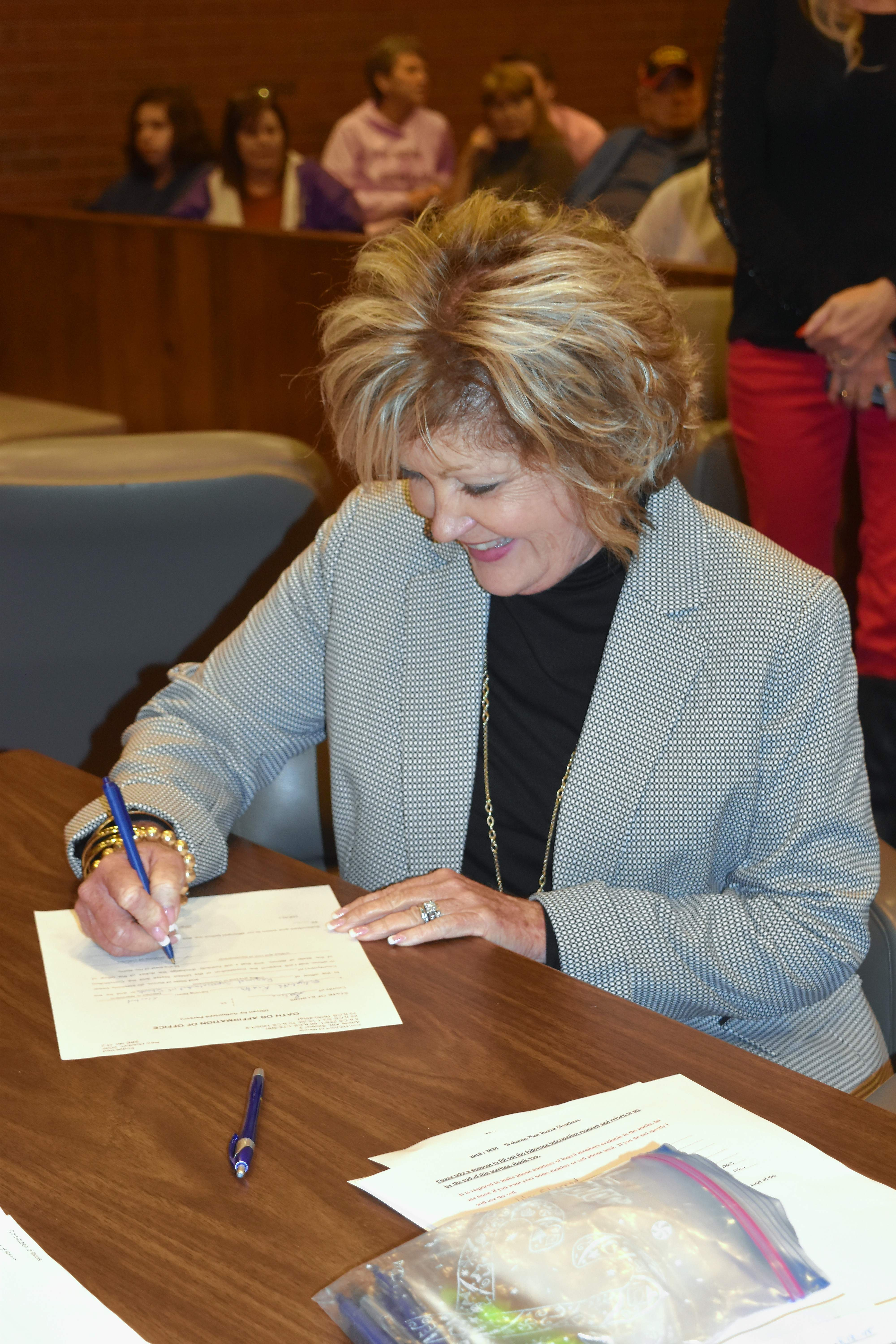 Regional Superintendent of Education Beth Rister smiles as she signs a certificate signifying her installation into office Friday.