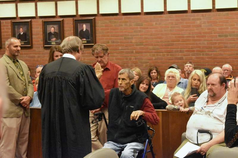Judge Walden Morris swears in Saline County Clerk Roger Craig Friday at the Saline County Courthouse.