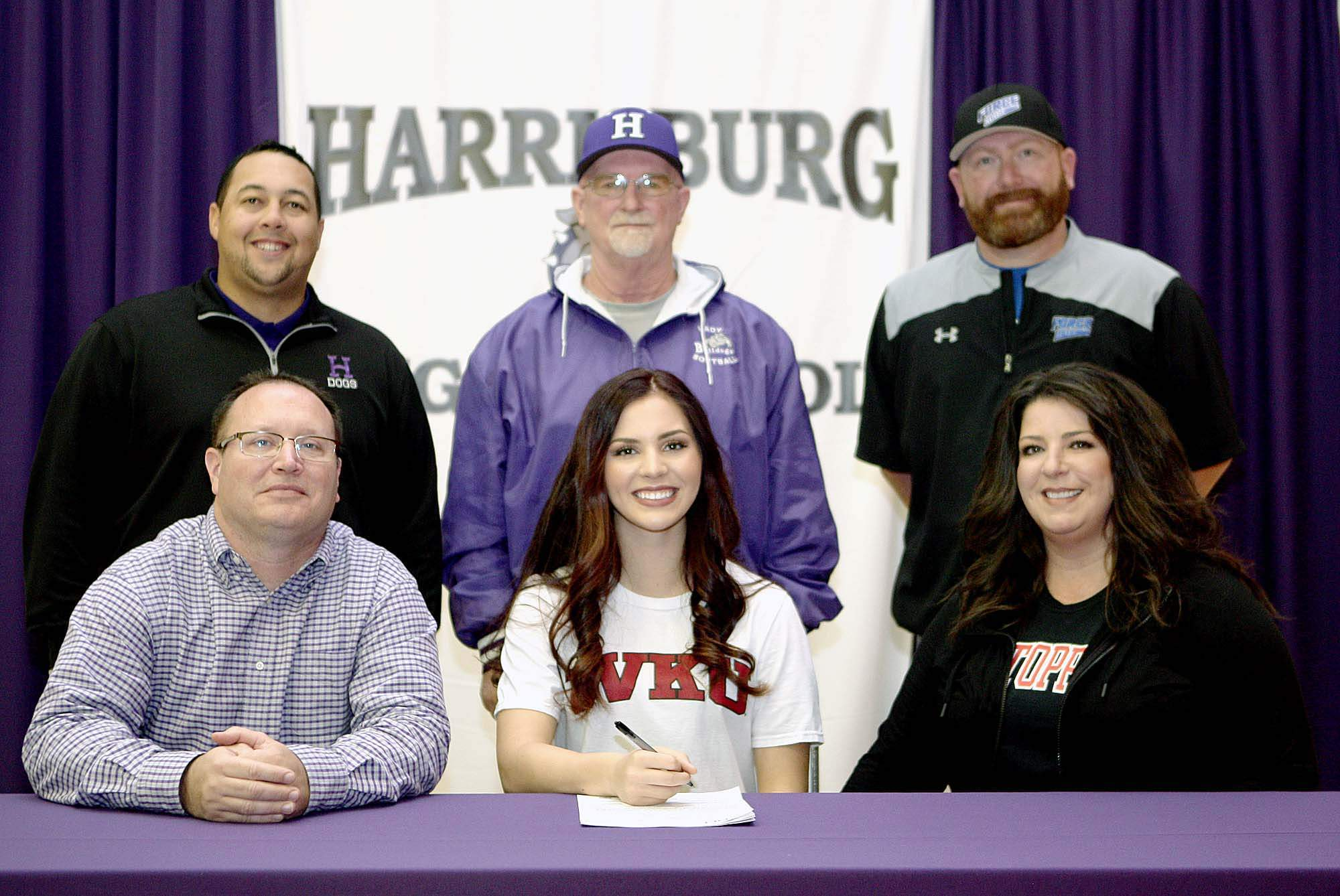 Madeline Rider, a senior at Harrisbug High School, signed a National Letter of Intent to continue her softball career at Western Kentucky University. Pictured with Rider are her father, Shannon and her mother Adrienne, along with, coaches (from left) Jake Stewart, Red Stafford and Brett Sullivan.