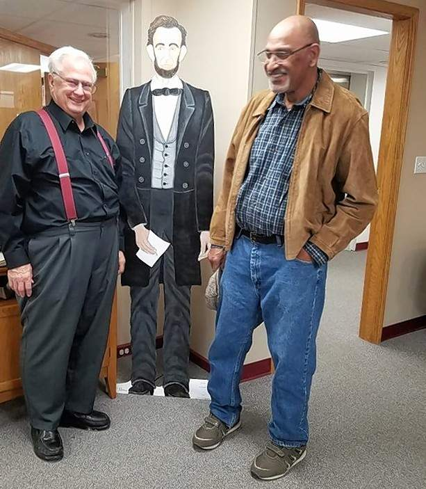 Harrisburg artist Jesse Rouse, right, stands with David Clemmons of Harrisburg and Rouse's life-size portrait of Abraham Lincoln in the downstairs community room at Harrisburg District Library.