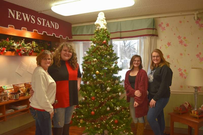 Above, from left, Saline Care Center Activity Director Tammy Smith and Harrisburg High School students Callie Oxford, Rachel Hutchison and Elle Behnke. At right, Saline Care Center Director Jason Quinn, right, supervises Christmas-themed window paintings provided by Southeastern Illinois College art students. Also pictured are SCC Activity Director Tammy Smith, far left, and SIC art professor Sara DeNeal.