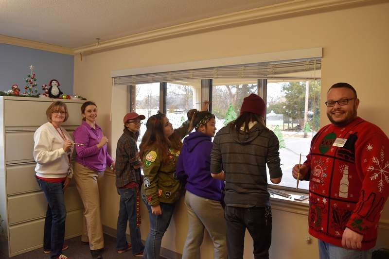 Saline Care Center Director Jason Quinn, right, supervises Christmas-themed window paintings provided by Southeastern Illinois College art students. Also pictured are SCC Activity Director Tammy Smith, far left, and SIC art professor Sara DeNeal.