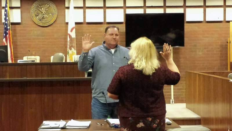 Saline County deputy clerk Julie Dunn swears in Ryan Lambert at the last county board meeting of 2018. Lambert fills the vacancy left by the late Roger Craig after Craig was elected county clerk.