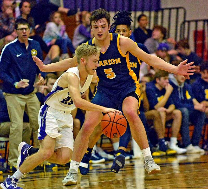 Marion's Jackson Connor maintains a pressing defense against Harrisburg's Will Gibbs Saturday night at Davenport Gymnasium.