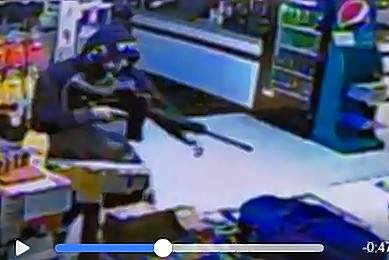 In this still image from security footage from Hathaway One Stop, an armed robber may be seen robbing the store Sunday evening.