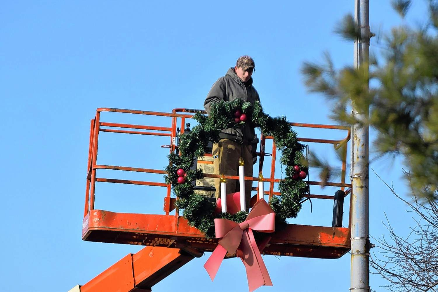This Harrisburg city worker removes a wreath from a lamppost Thursday.