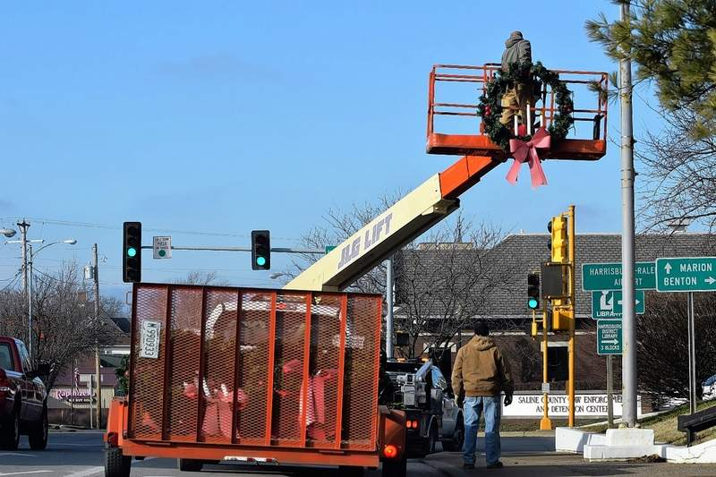 Harrisburg city workers quickly remove Christmas decorations hanging around the city.