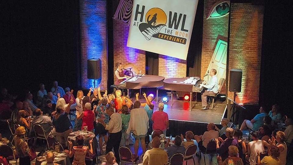 Two pianists duel at a Howl at the Moon performance.