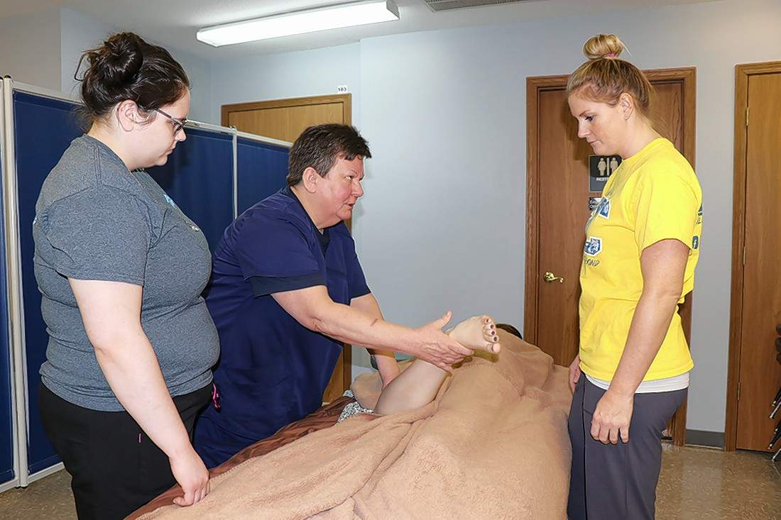 SIC massage therapy instructor Sheila Brown demonstrates joint movements and shaking to students Katherine Woodard (left) of Carmi and Sarah Welch of McLeansboro. The technique can be used to increase range of motion.