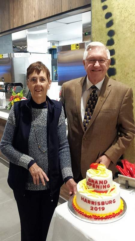 Mary and John Moreland stand next to a cake commemorating the grand opening.