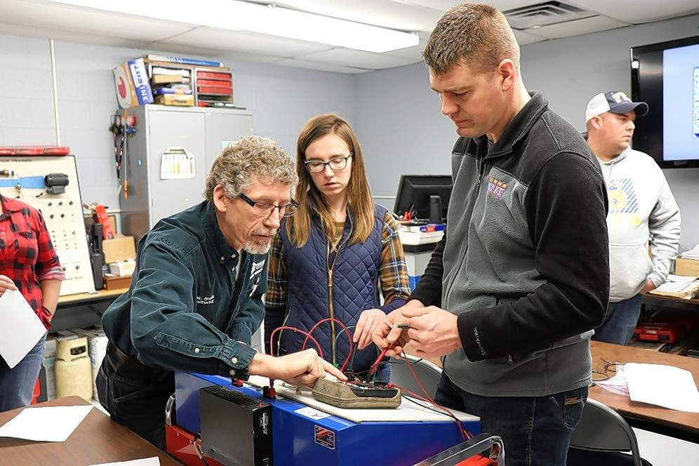 SIC powersports and diesel instructor Ralph Boots assists Vienna Ag instructors Vanessa Williams and Jason West with testing voltage on a circuit they built as part of an electrical training experiment.