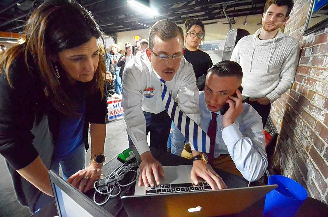 New Marion mayor Mike Absher, in tie, checks his laptop for the latest election results at Pookie's Beer, Burgers and Bocci Tuesday night. To the left is campaign manager Joni Barwick and seated is Justin Maze, a member of Absher's committee.