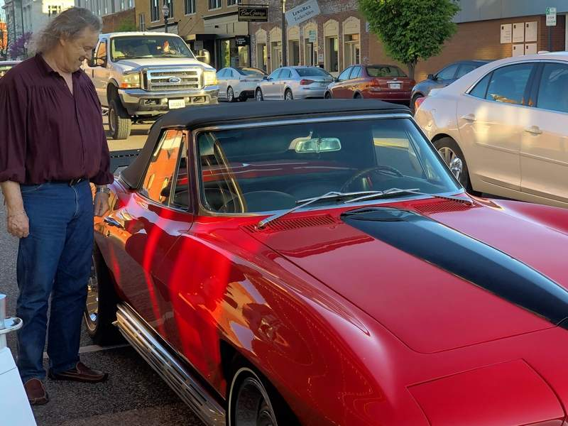 "Actor Les Lannom smiles as he looks at a Corvette Stingray similar to one he drove during the filming of the 1978 cult classic ""Stingray."""