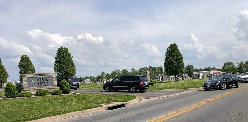 The funeral procession turns into the gates of Rose Hill Cemetery in Marion, where Mayor Bob Butler is being laid to rest.