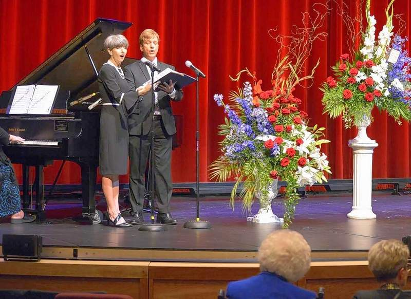 """Beth Butler, the only daughter of Bob and Louetta Butler, and family friend Jared Garrison honor her late father with a duet of """"A Flower Remembered,"""" to begin the hour-long service at Marion's Cultural & Civic Center."""