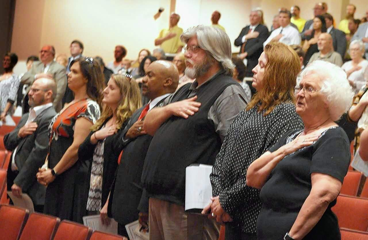 The crowd in attendance at Marion Mayor Robert Butler's memorial service Tuesday rises to join in singing the Star Spangled Banner led by Marion High School student Victoria Shore during the presentation of colors by the Junior Air Force ROTC.