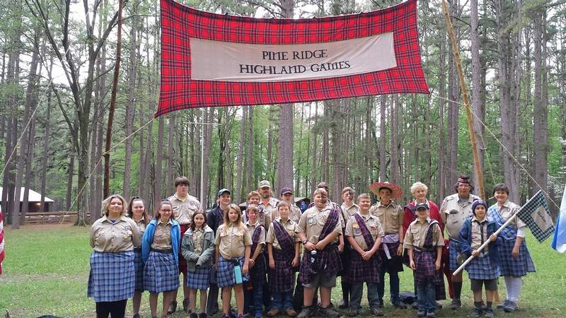 Members of Scouts BSA Troops 156B and 156G stand with the banner of the Spring Camporee Highland Games at Pine Ridge Scout Camp near Makanda.