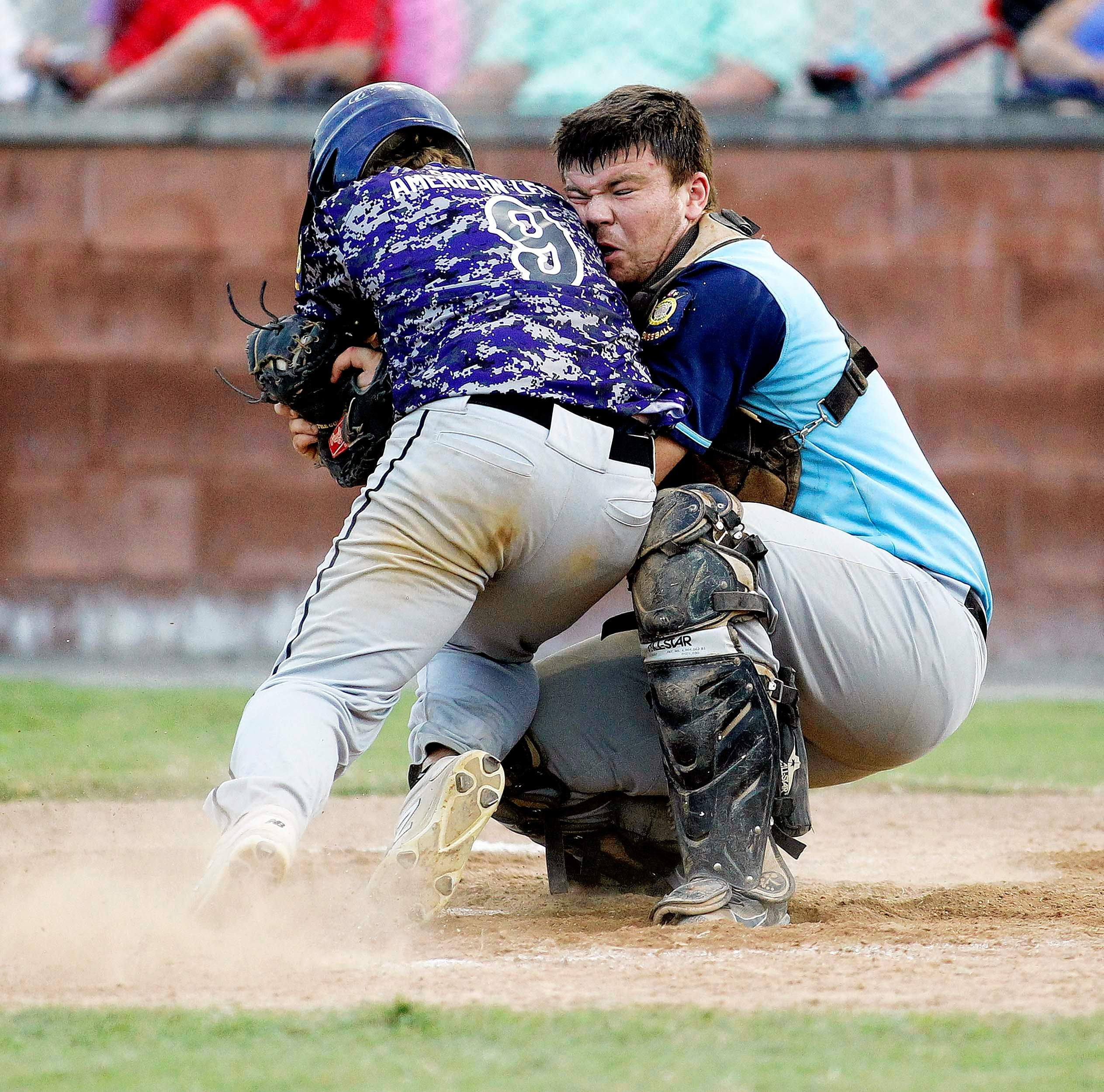 """Michael """"Spyder"""" Dann won a second place from The Associated Press for this photo of Harrisburg Post 167's Bronson Stanley trying to run over Carmi Post 224 catcher Travis Black as Stanley was tagging up on a flyball. Black hung on."""