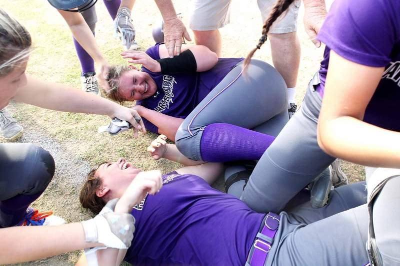 Lydia Miller (right) is mobbed by teammates after the junior drove in the winning two runs to beat Eldorado 8-7 in the Class 2A Regional Championship Friday in Harrisburg.