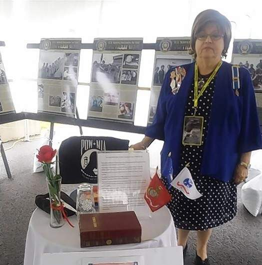 Sheila Albright, Michael Hillegas Chapter, DAR, explains the significance of items on the Missing Man Table at the Vietnam War Moving Wall.