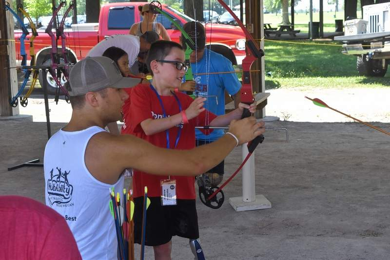 Andrew Gonzalez, 10, of Kingsland, Georgia gets a helping hand on how to operate the bow from archery instructor Preston Wright of Augusta, Georgia.