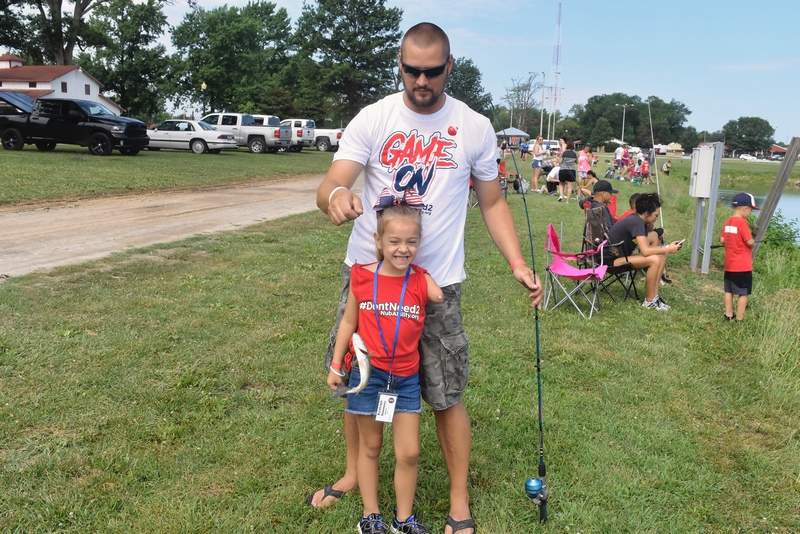 Kynleigh Simmons, 5, of Marion, shows off her big catch with her father, Justin, standing behind her. The youngster helped haul in four fish Thursday morning, including bass and catfish.