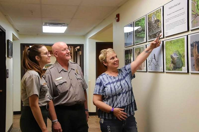Teresa Fouke (right) shows Breanna Whitley and Tim Bischoff photos in the gallery at the Rend Lake Visitors Center.