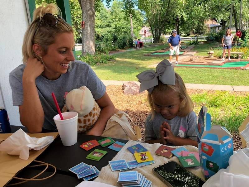 """Mallory Hill smiles as her daughter, Giovanna, shyly reveals the identity of her kidney donor.  """"Daddy,"""" she said, grinning, then going back to her card game while waiting for players to finish the tournament fundraiser in ehr honor on Saturday."""