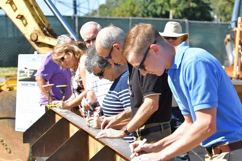 Ferrell Hospital Board member Austin Rahmoeller joins others signing the main beam for the hospital's expansion project Wednesday afternoon.