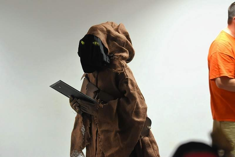 A junior cosplayer walks away with an award in a handcrafted Jawa costume.