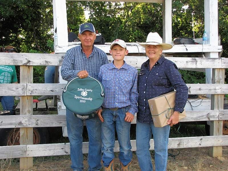 Tate Miller, winner of the 2019 Saline County 4-H Horse & Pony Sportsmanship Award, is pictured with Larry and Valerie Allen, award sponsors.