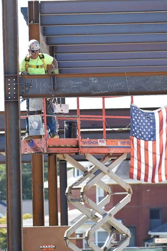 A construction worker looks down at the main beam of the Ferrell Hospital expansion, signed by members of the Eldorado community, which was put into place Thursday morning.