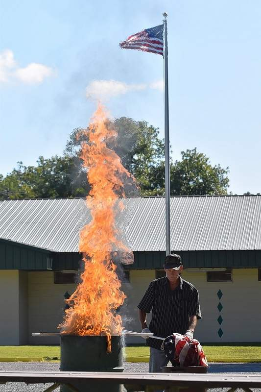Legion member Terry Ferrell retires old U.S. flags the correct way, after the new flag and flagpole were dedicated.