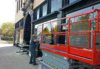 Ben Donley of Glass Doctor in Harrisburg loads a new window onto a hydraulic scaffold Monday.