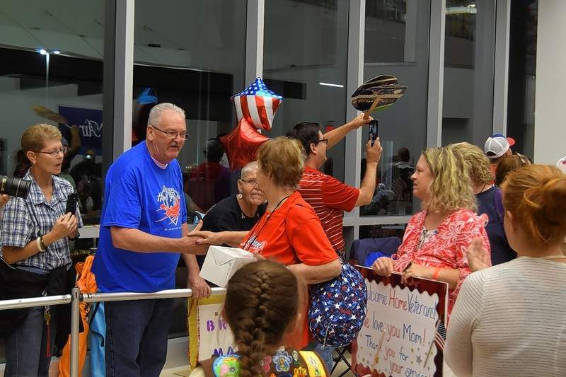 LEFT: Joanne Wathen, a Carrier Mills Navy veteran, is thanked for her service at Honor Flight's return Tuesday night. RIGHT: Gary Stricklin of Harrisburg, a Vietnam War Army veteran, points to a crowd member in greeting, who points back while taking his photo during Honor Flight's return.