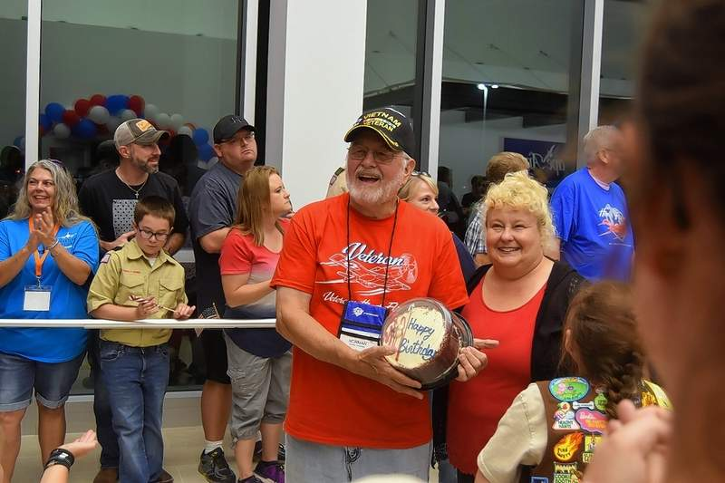 Norman Alexander, a Vietnam Air Force veteran, holds up a birthday cake he received during Honor Flight. With him is his daughter Robin Johnston.