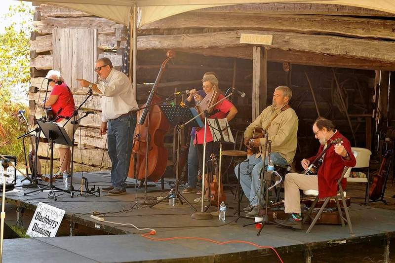 Emcee Eric Gregg announces the group 'Blackberry Blossoms,' one of five musical groups that performed at the Bluegrass and Barbecue Festival, Saturday at the Saline Creek Pioneer Village and Museum in Harrisburg.