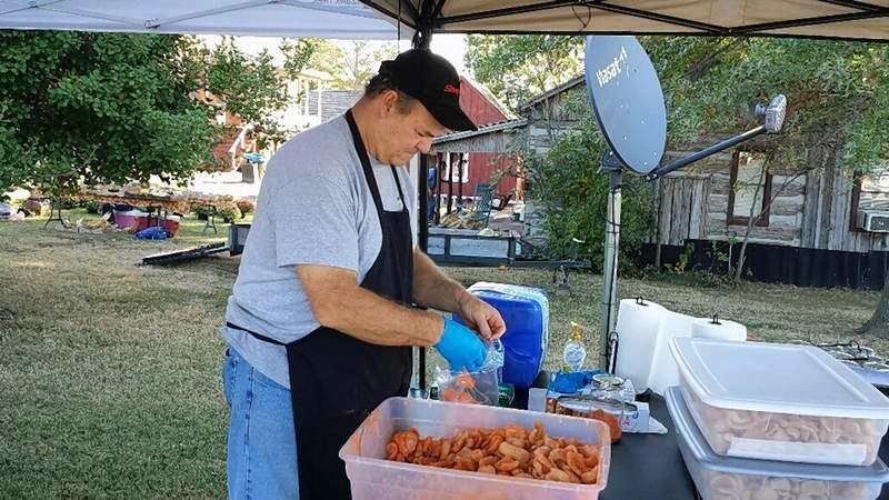 Wayne Beal of Harrisburg seasons a fresh batch of barbecue pork rinds.