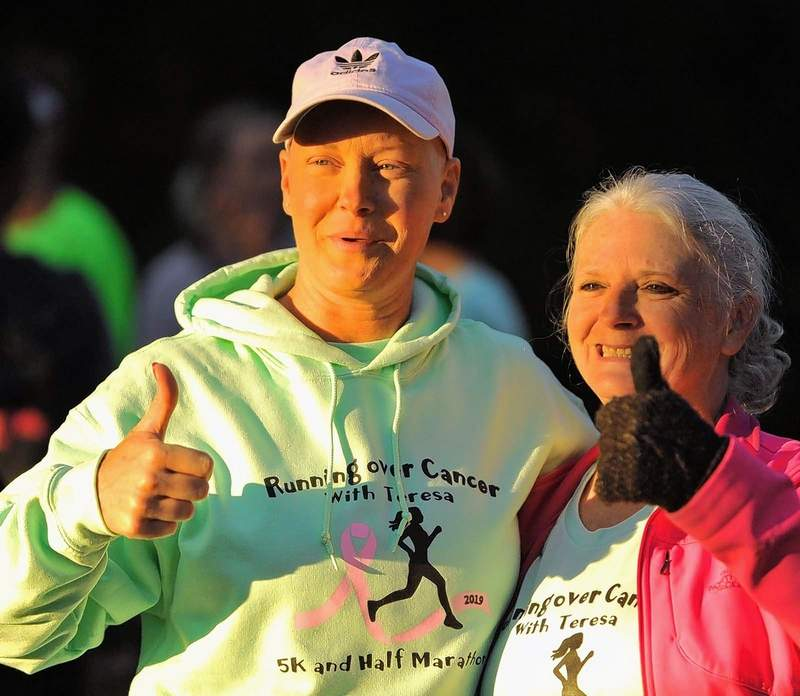 Teresa Hathaway, left, poses for a photo with a supporter just prior to the start of the half marathon Saturday morning at Sahara Woods.