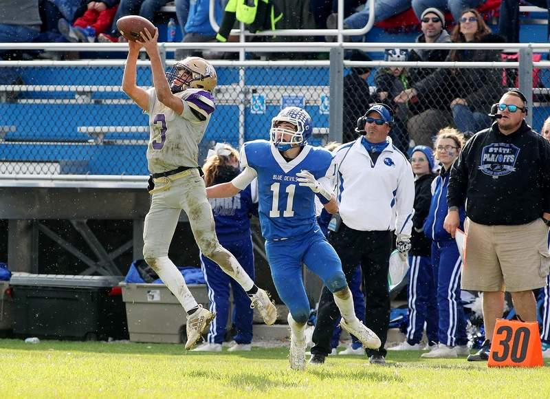 Eldorado's Ezra Burtis comes up with this interception in front of Bismark-Henning's Mason Hackman (11) and the rest of the Blue Devil sideline Saturday in the first round of the IHSA Class 2A Playoffs.